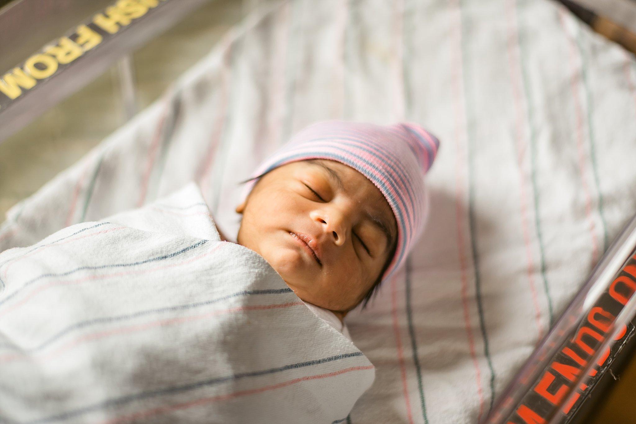 Newborn baby boy with hospital hat on