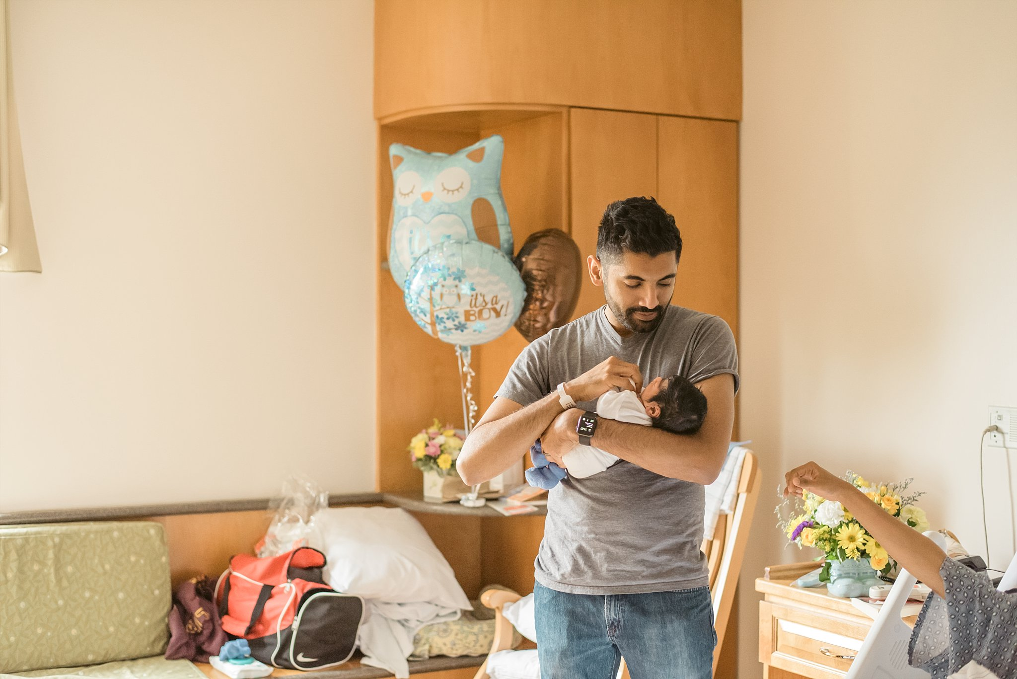 Dad holding baby in hospital room