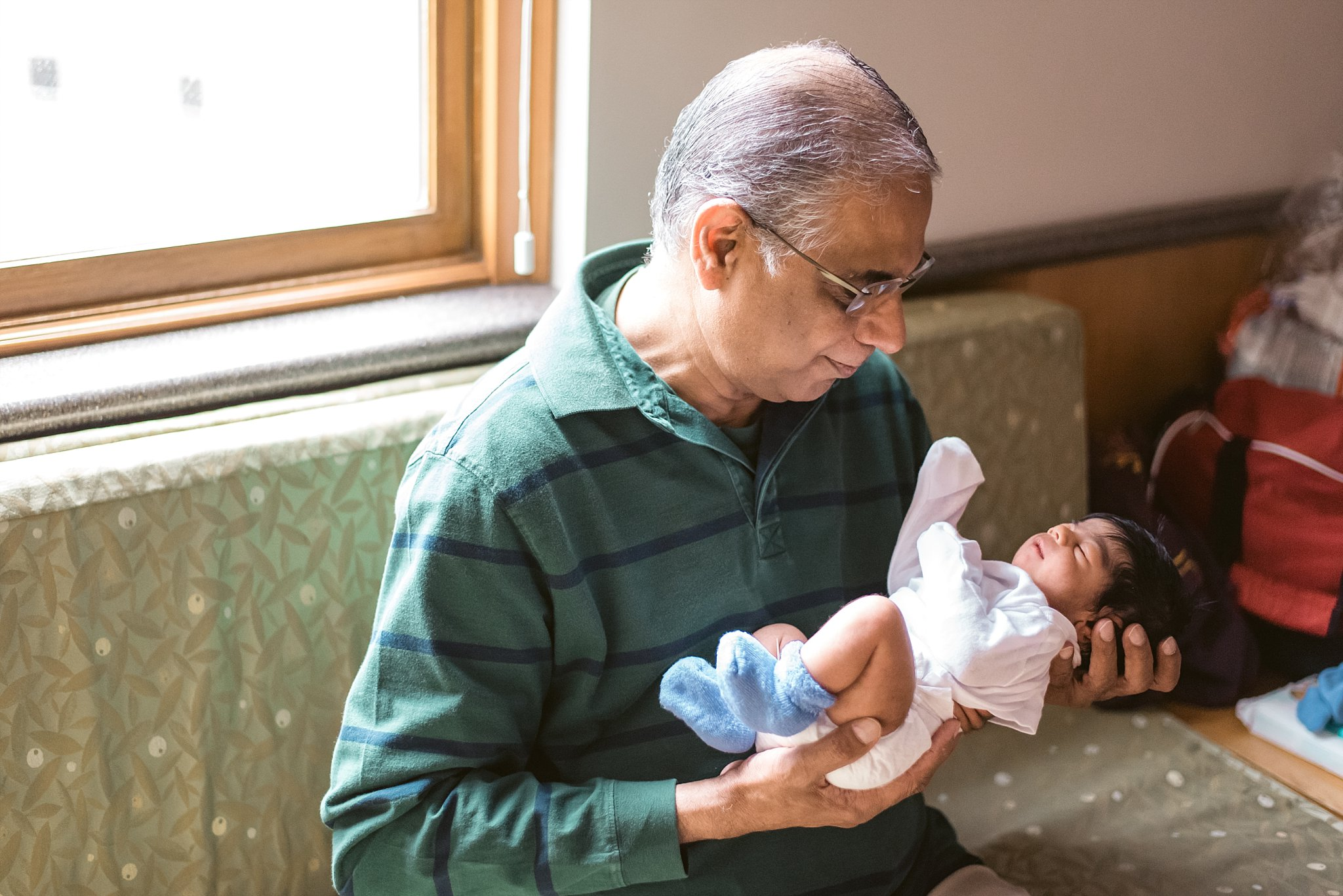 grandfather holding newborn baby