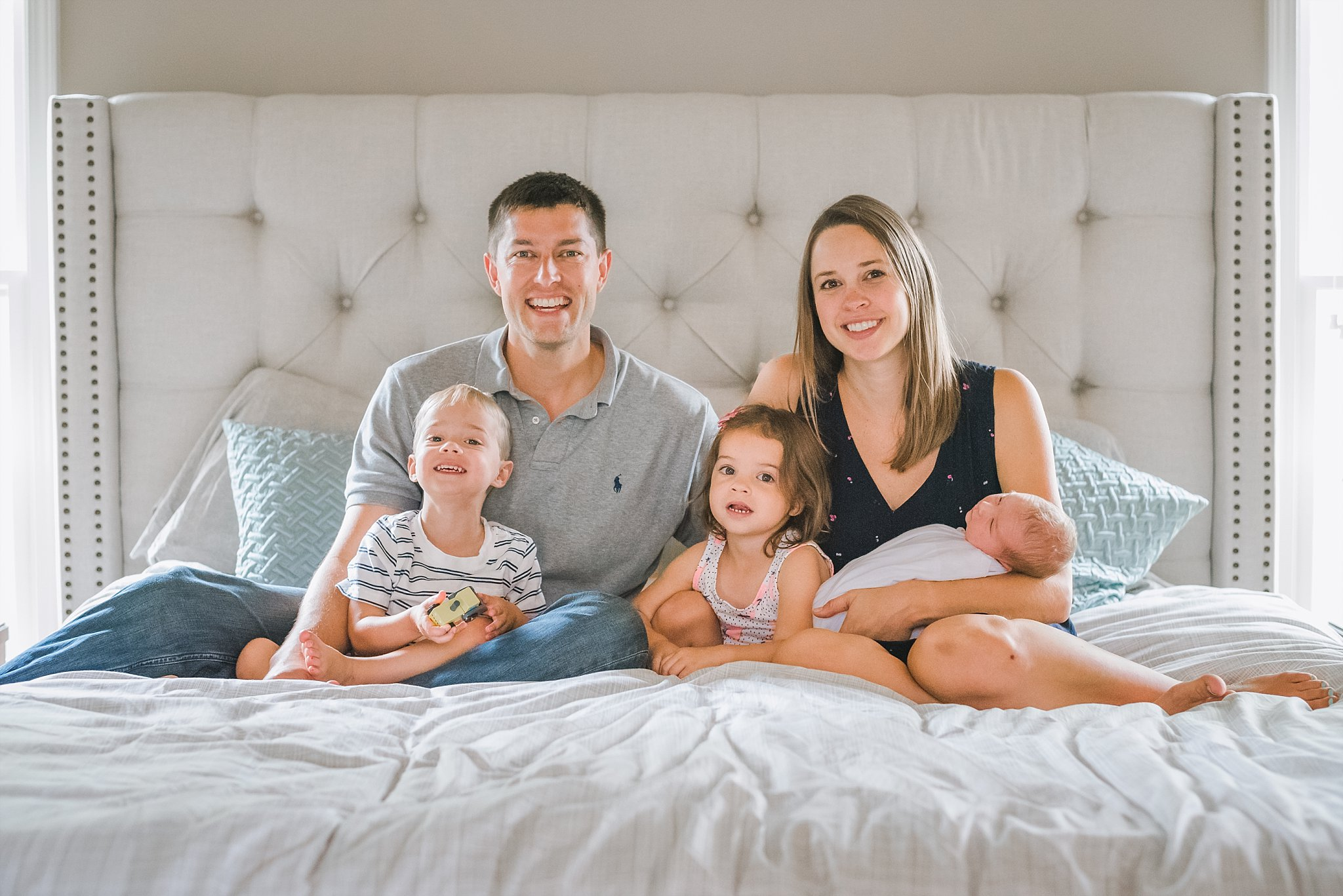 New family of five on master bed at lifestyle newborn session in Woodstock, GA