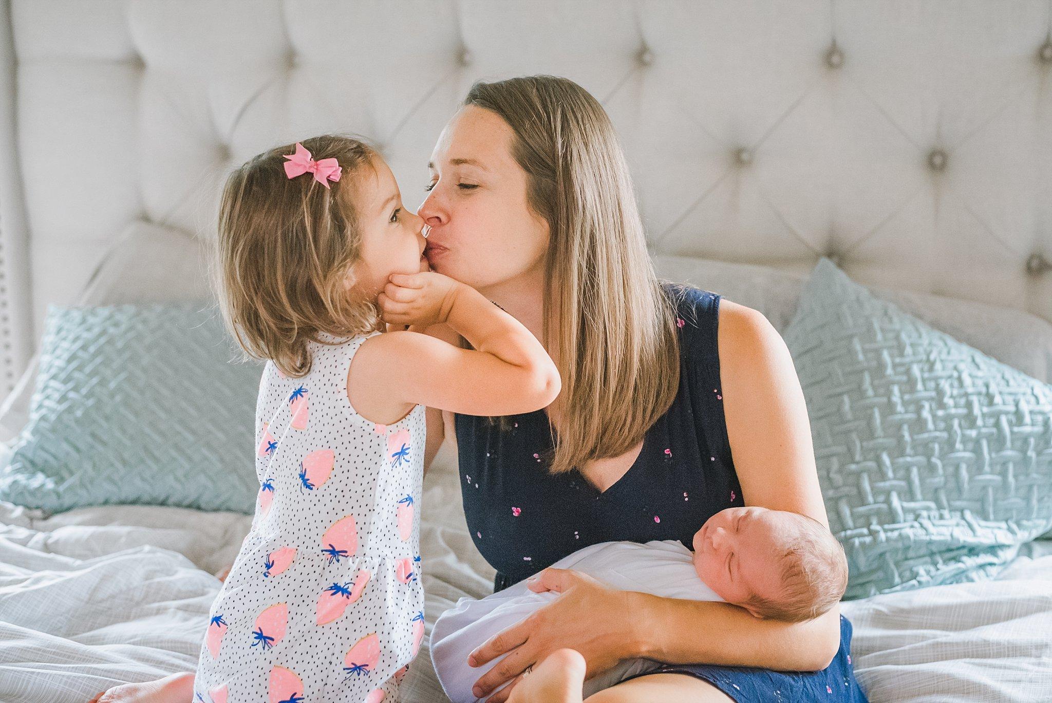 toddler girl kissing mom holding newborn baby