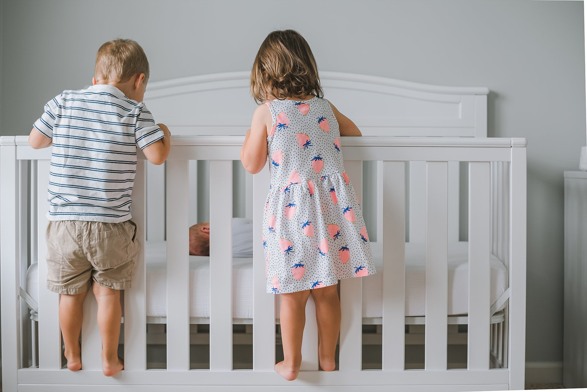 twins standing on crib looking at newborn baby boy