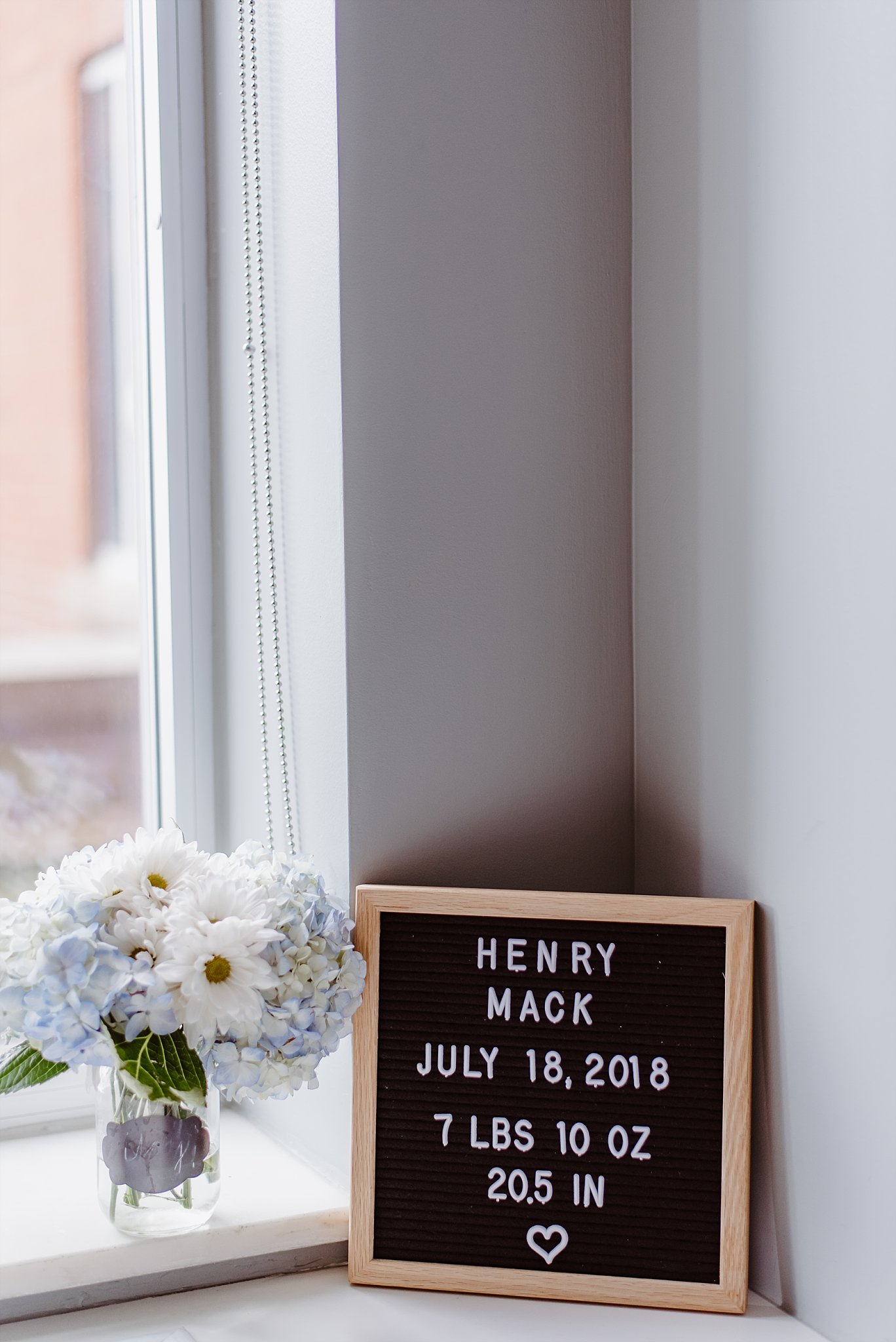 letterboard next to flowers with baby's name birth date and weight