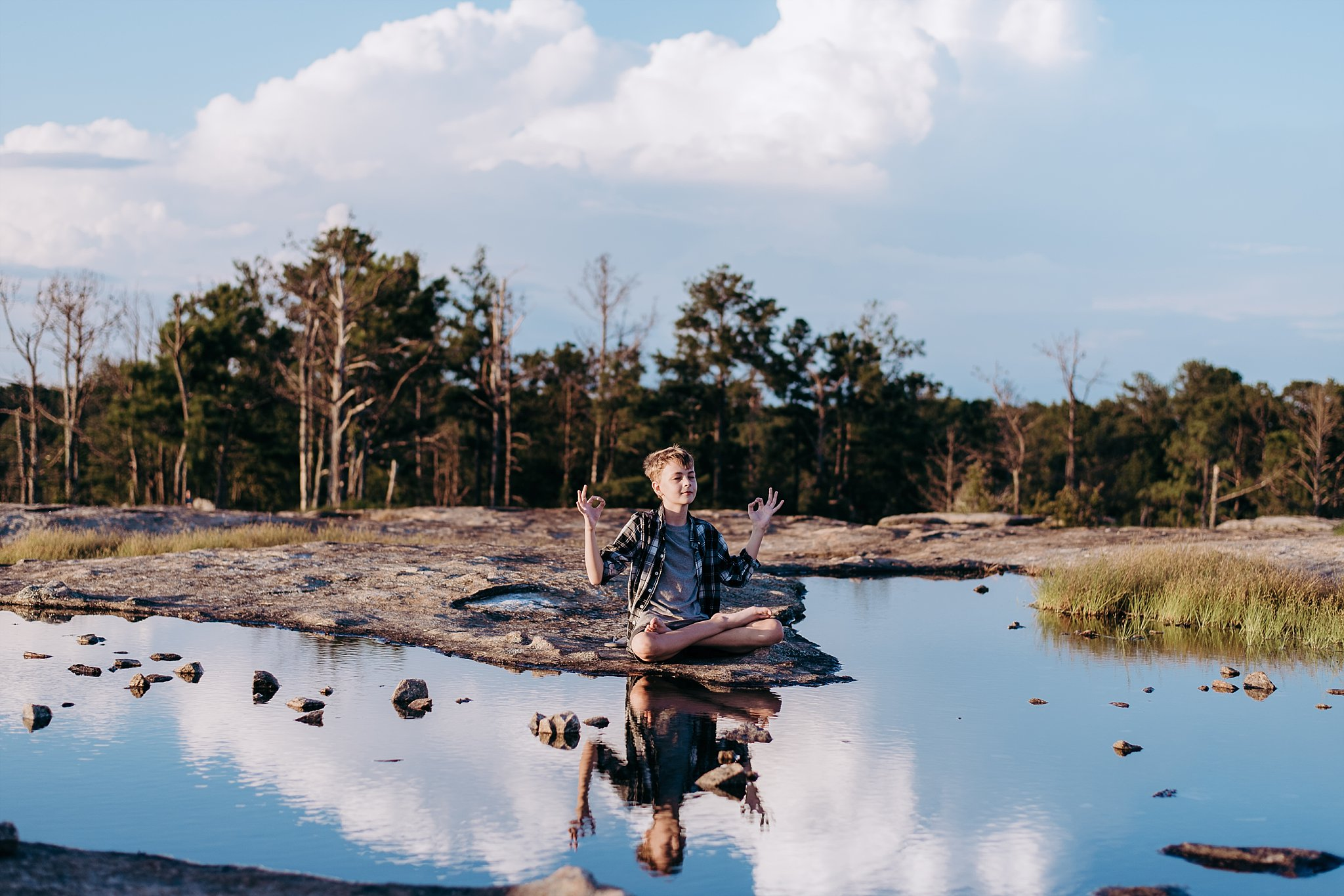 reflection of boy meditating at Arabia Mountain Atlanta