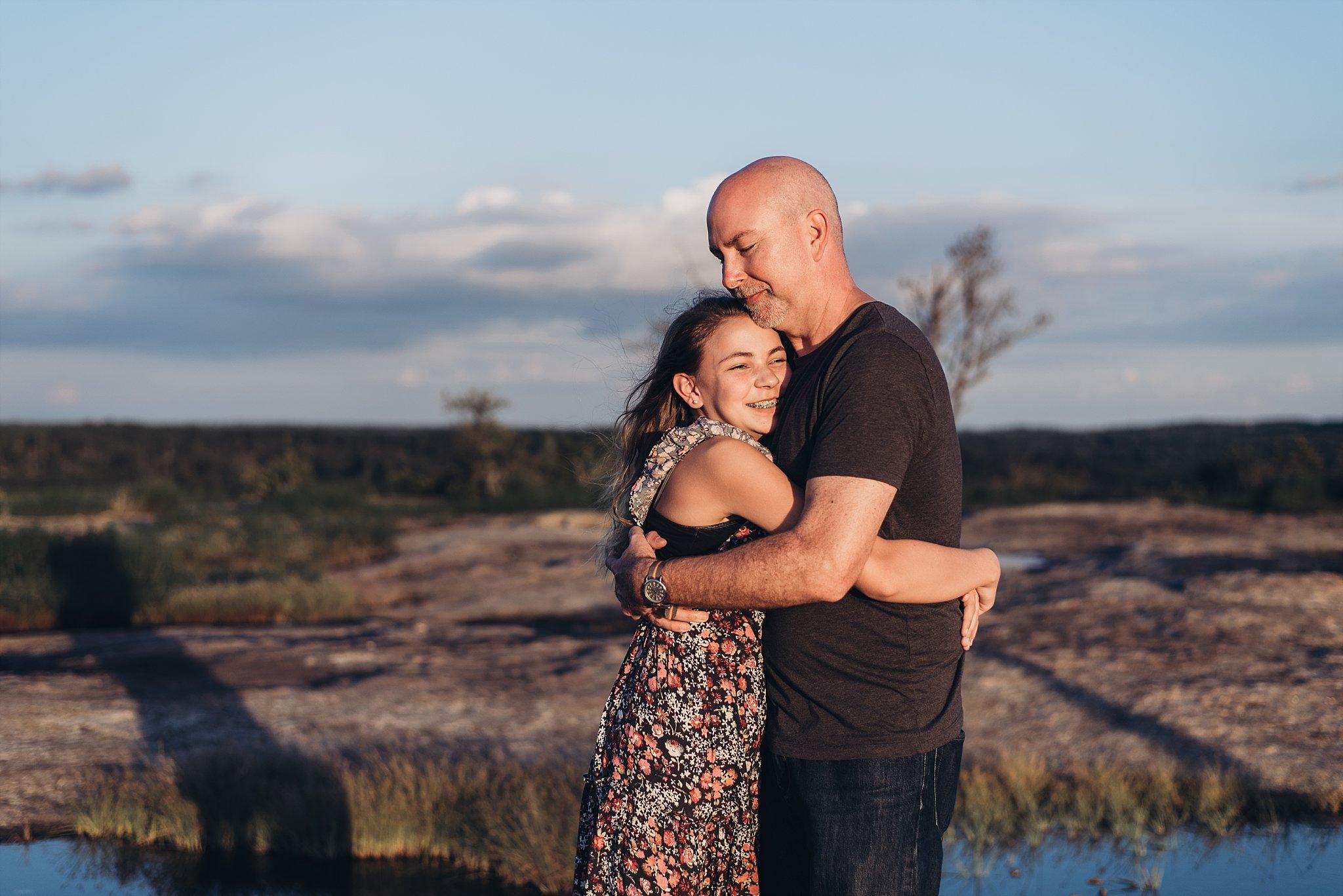 daughter hugging dad at Arabia Mountain top