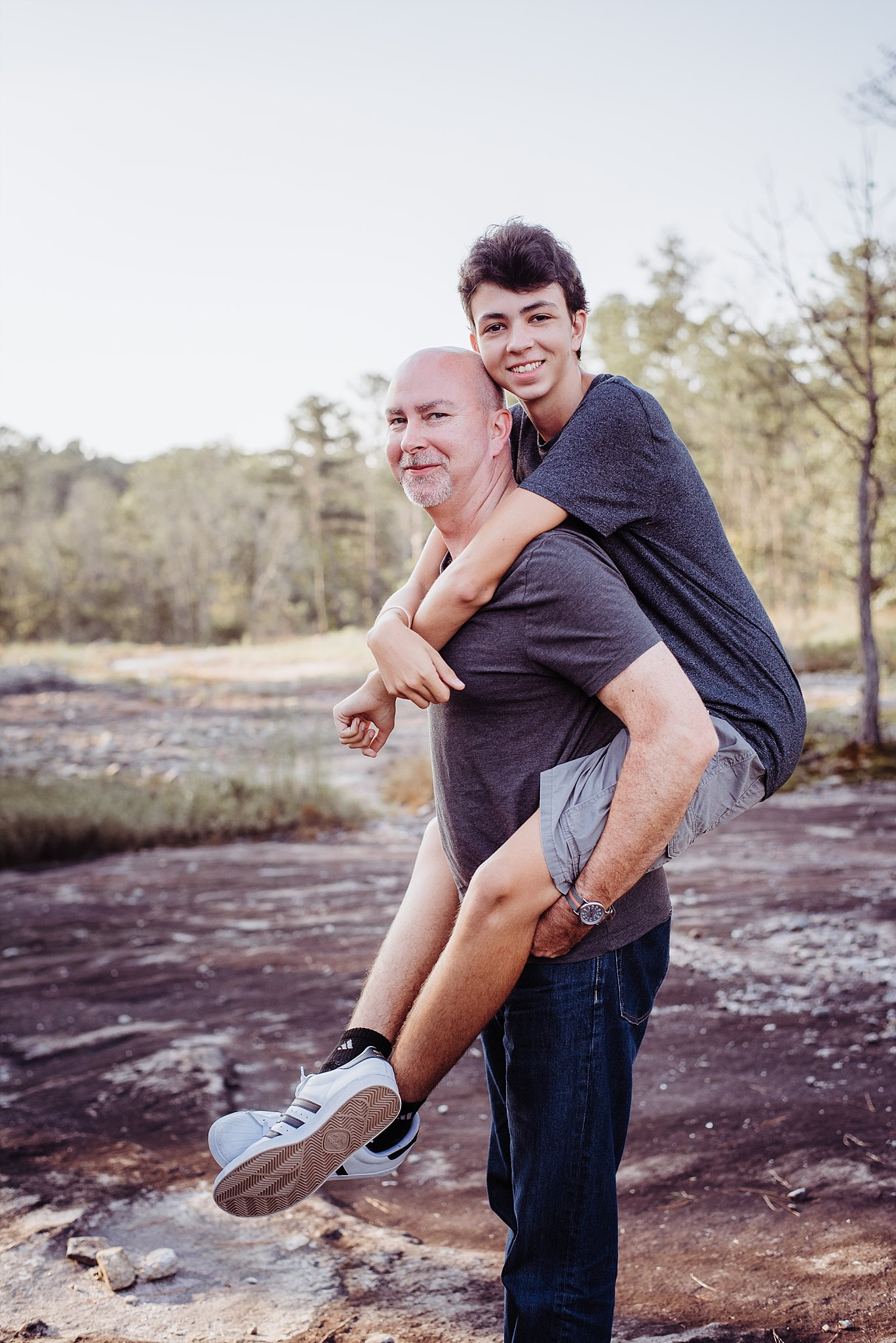 teenage son piggyback with dad Arabia Mountain Atlanta