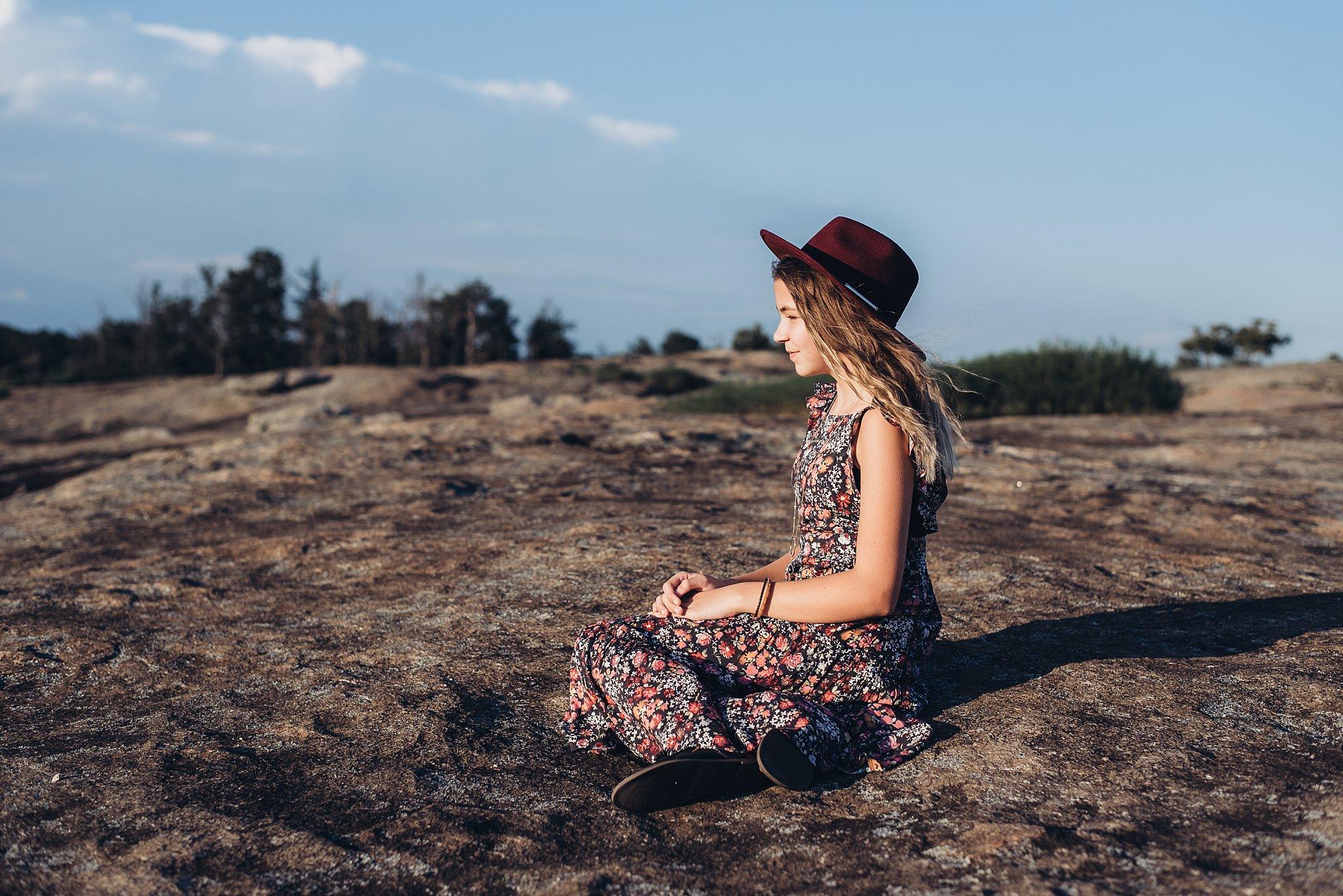 girl sitting wearing red hat looking out at Arabia Mountain Atlanta