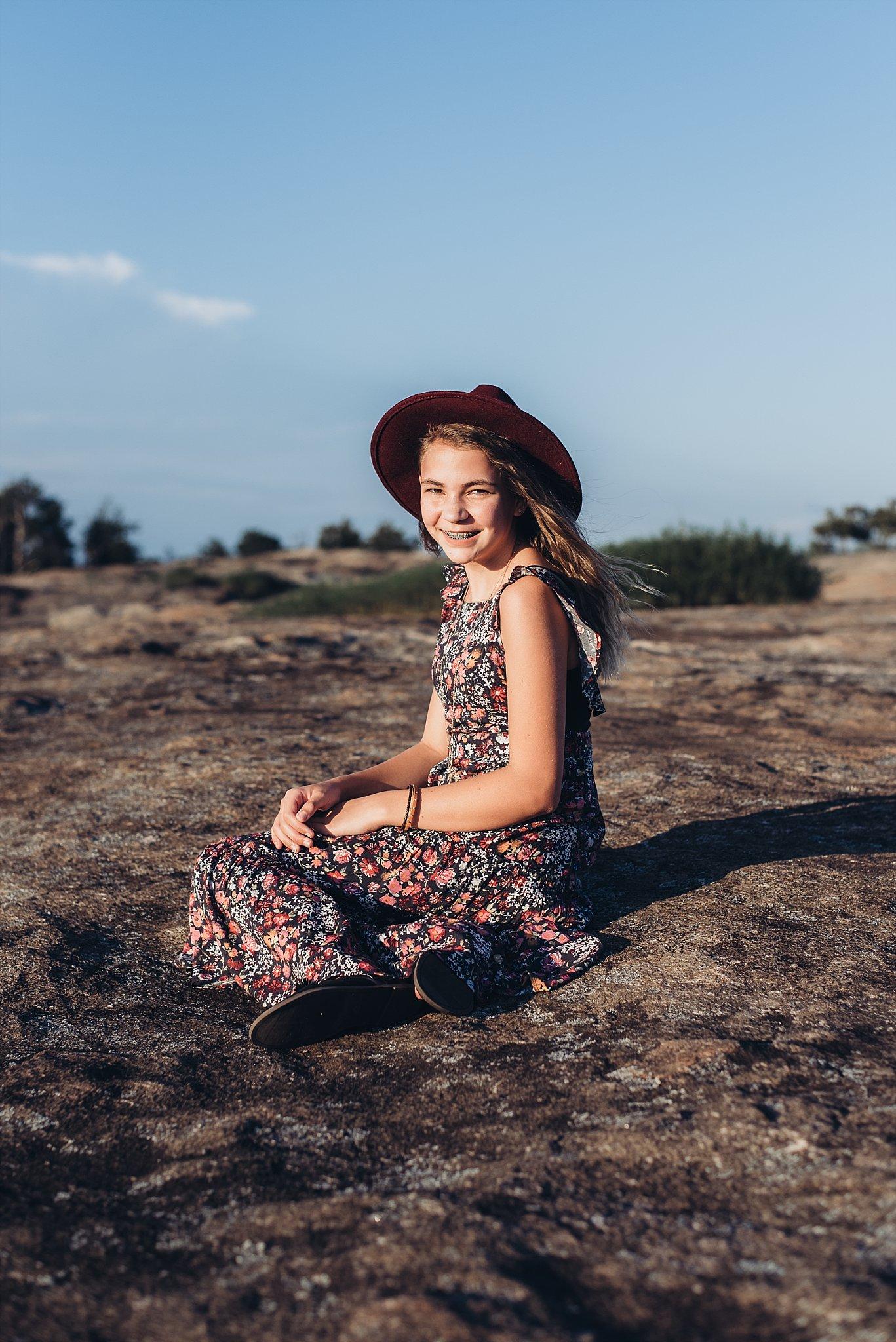 Girl wearing red hat sitting at Arabia Mountain Atlanta
