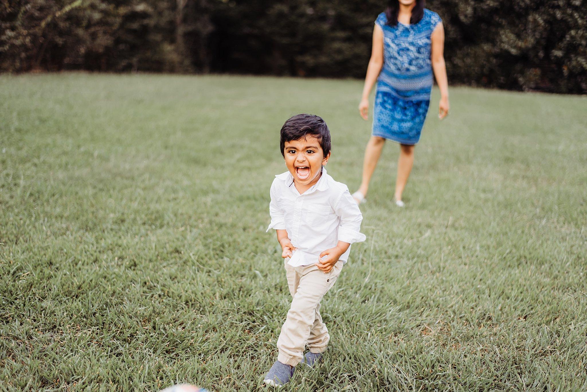toddler boy laughing and kicking ball