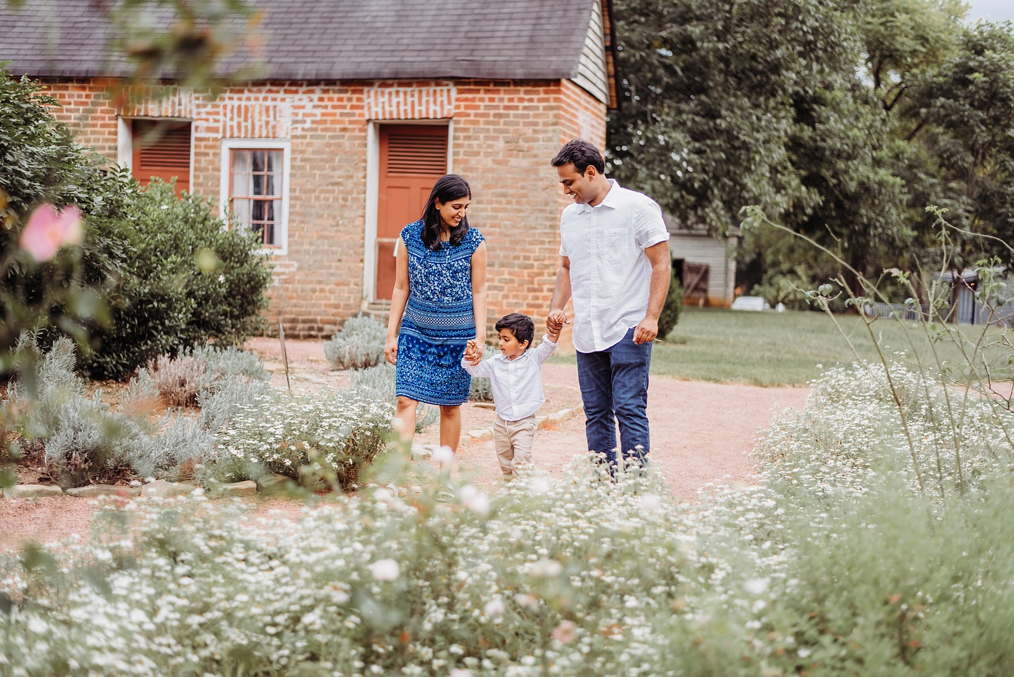 Family of 3 walking down path in gardens at Barrington Hall