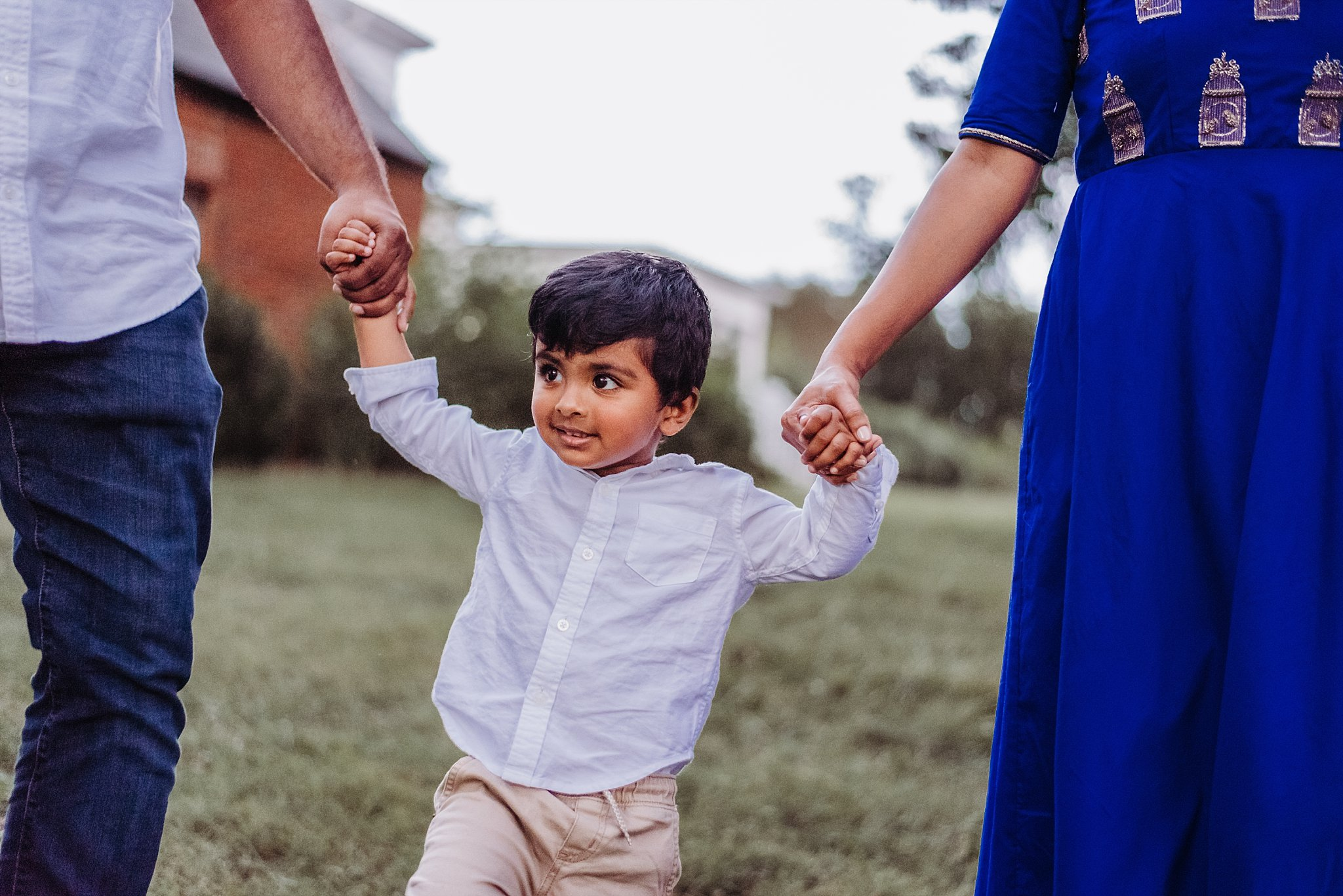 boy holding mom and dad's hands