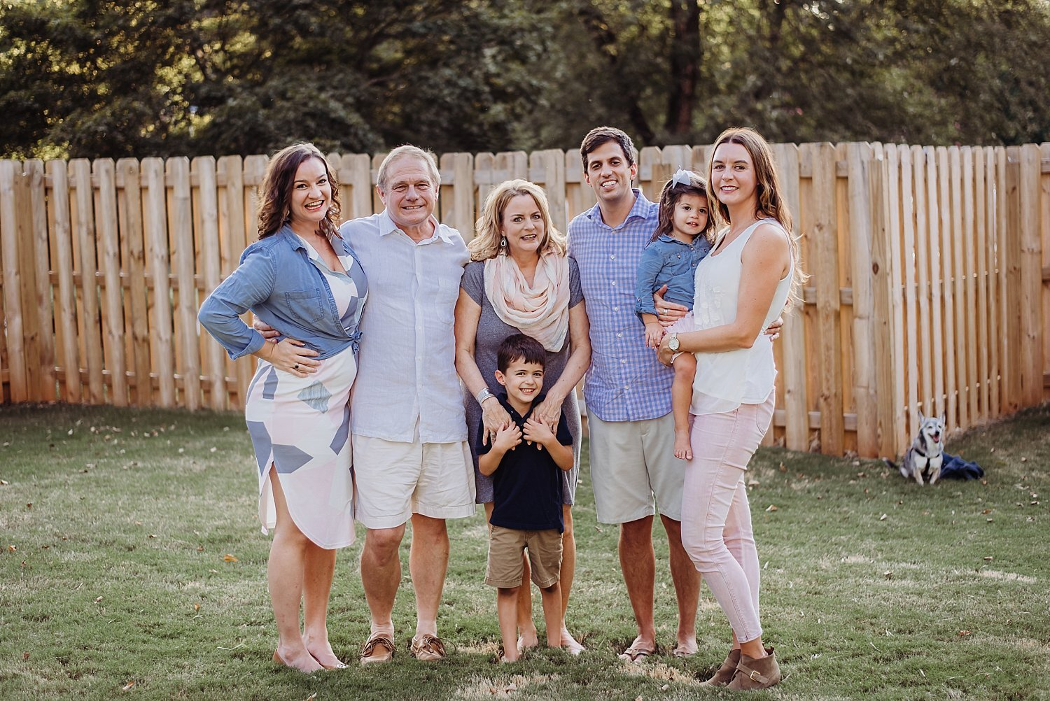 family photo in backyard with fence