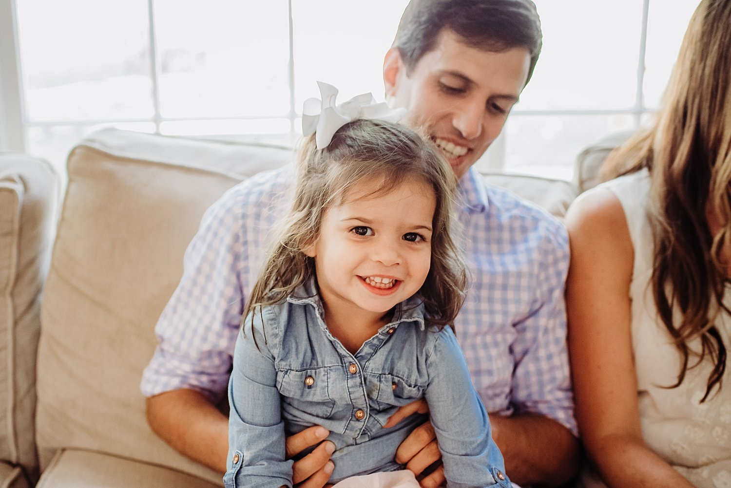 little girl sitting in dad's lap in-home family session Roswell, GA