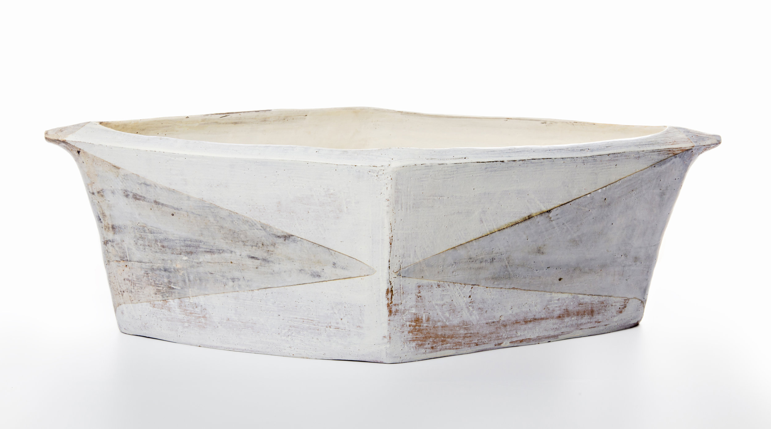 I make hand-built earthenware vessels that draw on the quiet, minimal forms of basic function, such as basins, troughs and baskets. Surfaces emphasize the subtleties of material, process and firing as the primary decorative elements – dragged grog, finger marks, the layering of slips and terra sigillata, and the dulled whites and blacks that come from reduction firing at a low temperature.  Smaller pieces like plates, cups, mugs and bowls are wheel-thrown, then scraped and pared down in form and reduction fired. Most recently I have been pulling from my long love of textiles to add pattern and color to this smaller work.