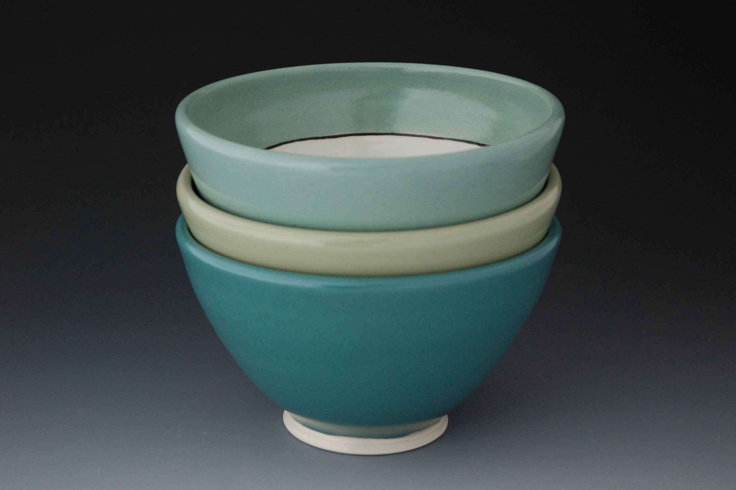 For me, pottery is a blending of both function and aesthetic. While I am very attuned to form, color, and design, drawing much inspiration from nature, I also pay attention to the way my work feels to hold and how easy it is to use. I want the handles of my mugs and pitchers to have a comfortable grip, for example, and I curve up the edges of my plates slightly so sauces don't run off and peas don't escape.  My pots each display evidence of the process I use to create them. In our society dominated by mass production and faceless corporations, handmade objects introduce human connections that I think we all yearn for. I want to draw the user in to look at the differences in subtle details of my work: the way the lines travel around the pot, the point at which they waver or are sharp and crisp or how the glaze breaks over a curve. I hope that the daily use of my ceramics will remind the user of the slower, handmade, and local aspect that they can choose for their lives.