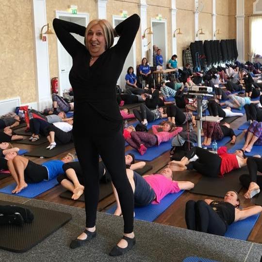 Kathy Corey mit fast allen Teilnehmern der Konferenz in einem Raum.
