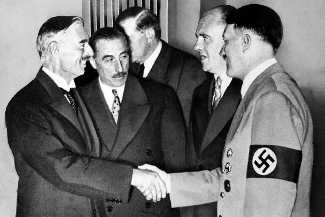 Neville Chamberlain shakes hands with Hitler at the summit to sign the Munich Agreement (1938)