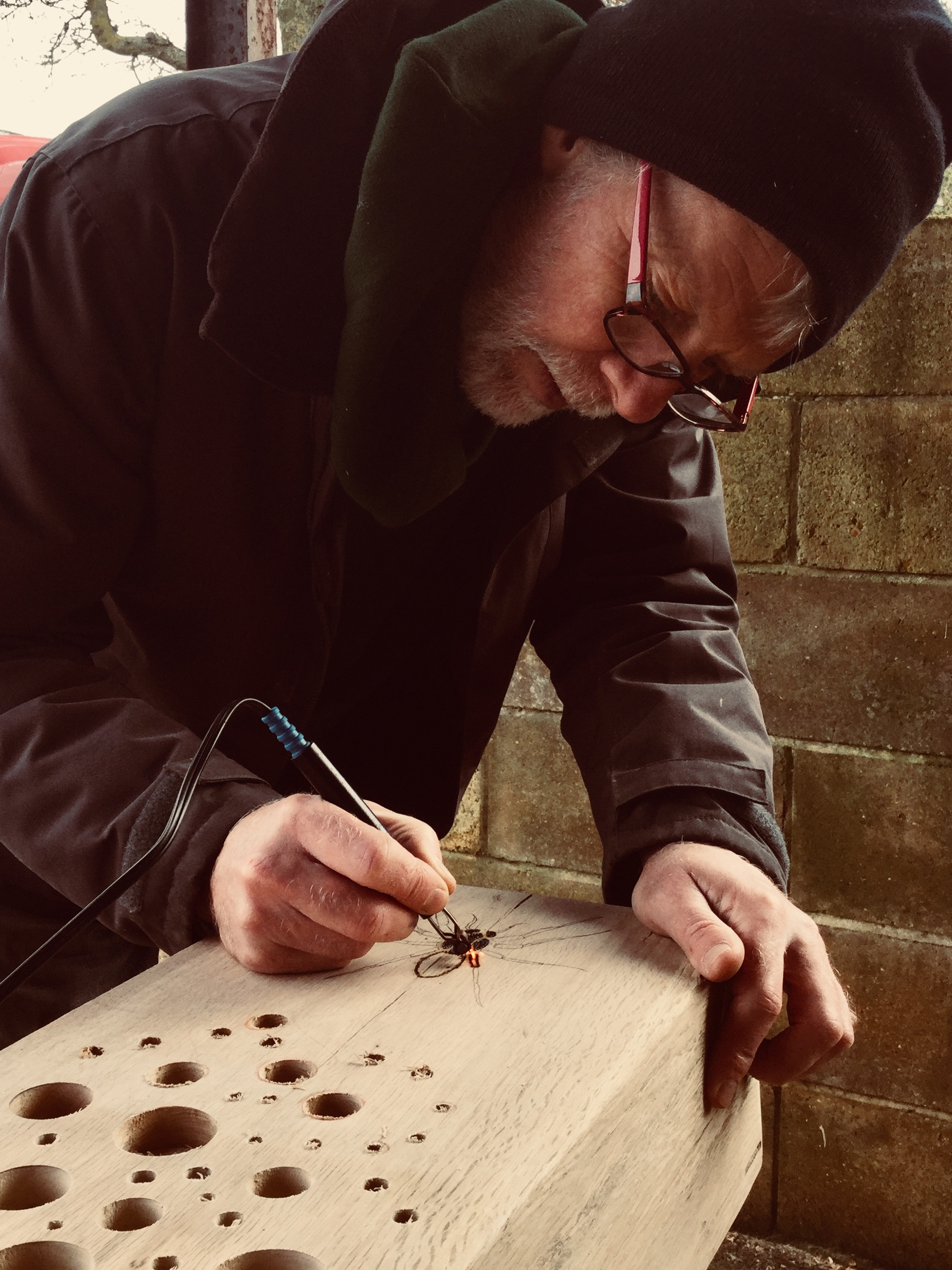 Artist Nigel George pyrographing designs on to each BioTotem