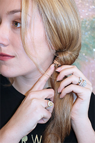 Place the hair tie here. Then use your fingers to brush down some hair from the twist until the tie is covered.