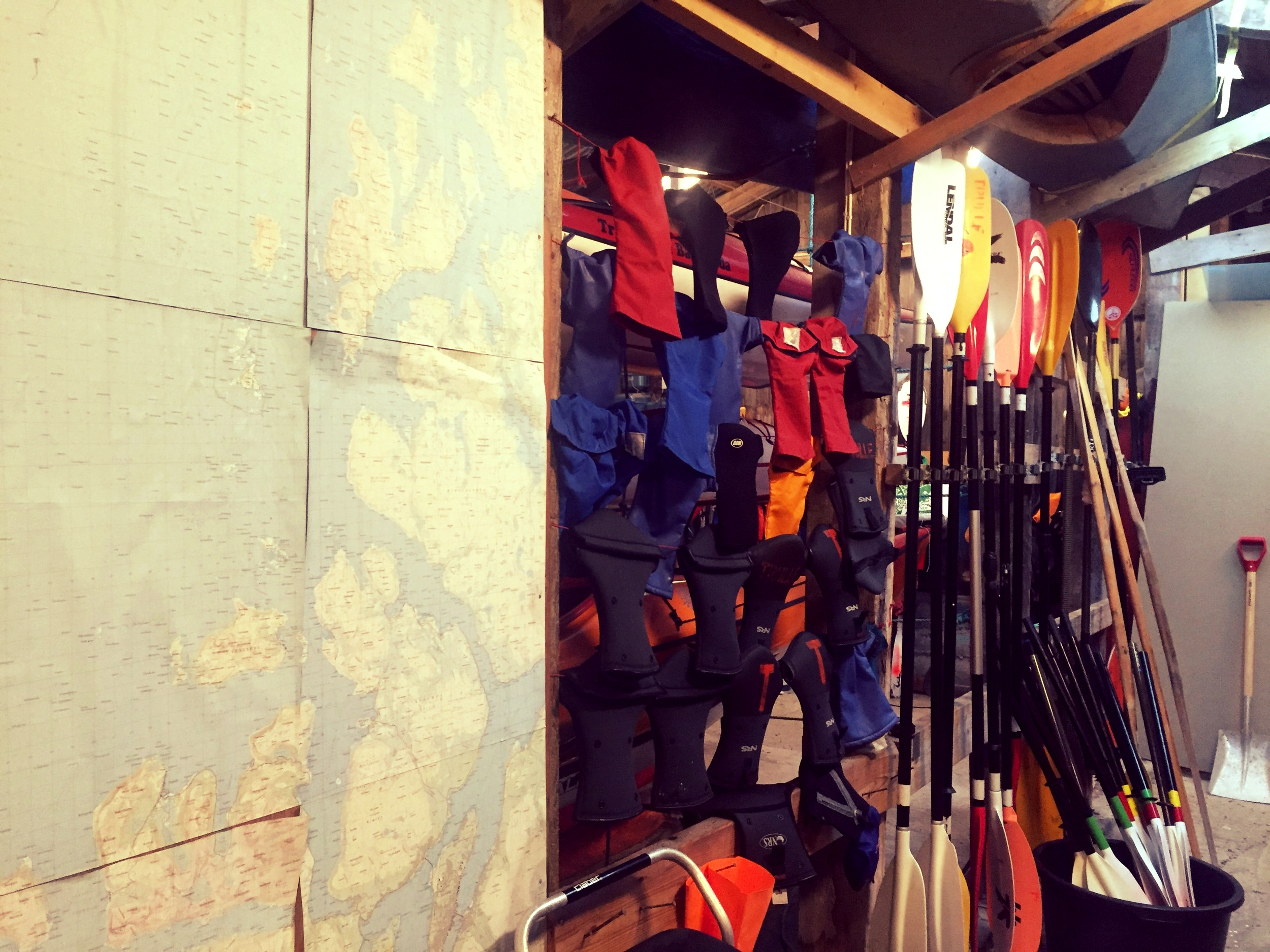 The inside of our boathouse with gear available for members, like pogies (mitts for your hands while padling) and padles, and a giant map of the area to plan your next paddling adventure.
