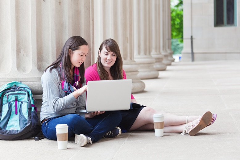 two-female-students-studying-outdoors-on-university-campus-with-laptop-computer-in-page.jpg