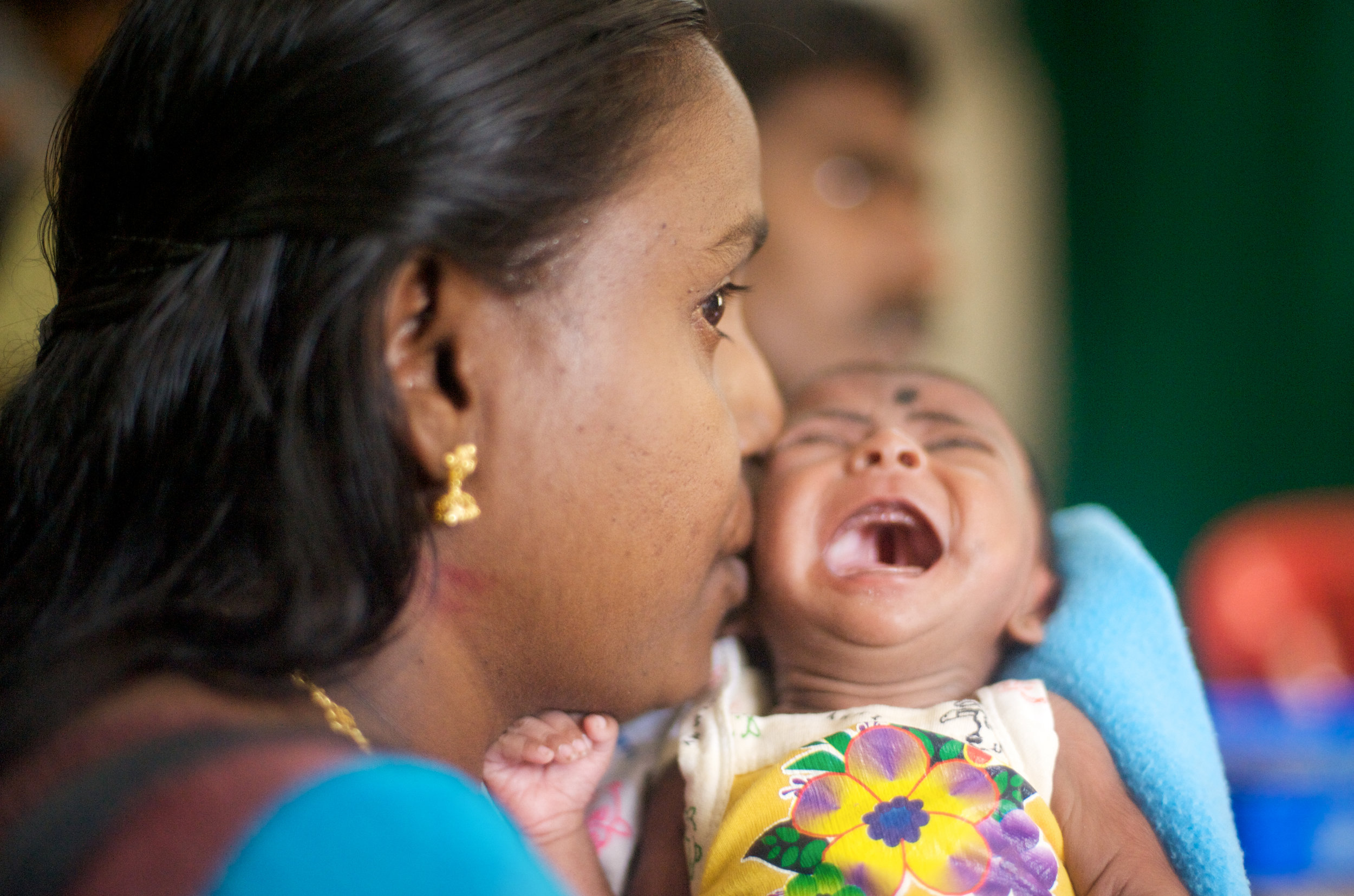 The consultation. A cleft palate, visible in the open mouth of a crying infant, brings a family to Dr. Adenwalla's clinic where he performs free corrective surgeries.