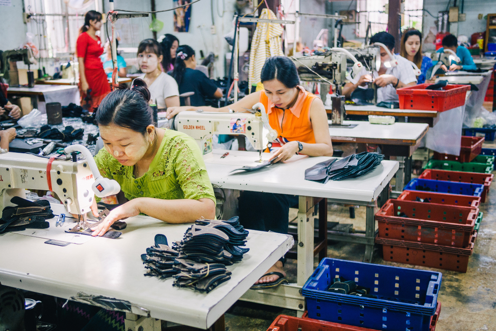 Burmese Female Migrant Workers Sewing Leather Shoes in thailand. catastrophe_OL/shutterstock