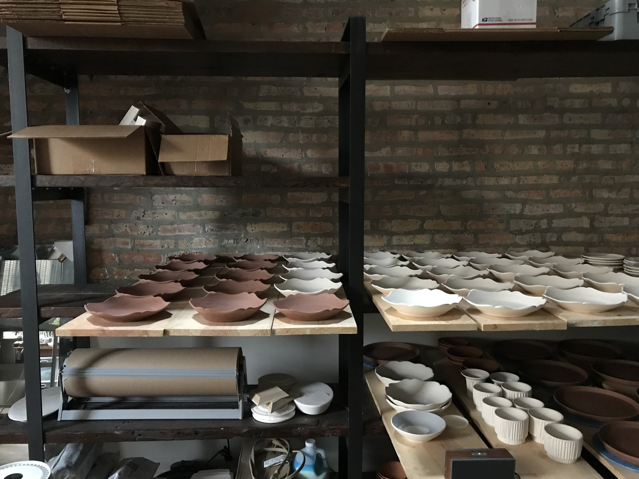The finished dishes drying and awaiting their first firing.