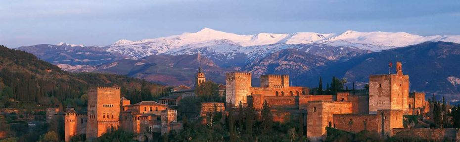 The sun sets on the Alhambra Palace, Granada. The snowy peaks of the Sierra Nevada in the back ground.