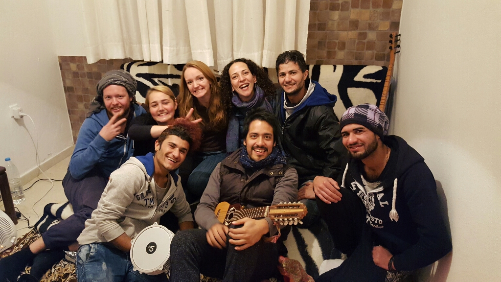 """One thing I love about this work is the people it brings together from all over the world. In this photo we had 3 Iraqis, an American, Mexican, Frenchman, Egyptian, and an Irish lass, jamming out to an Iraqi Saz and a Bolivian guitar. All in one small room in Greece. :)"""