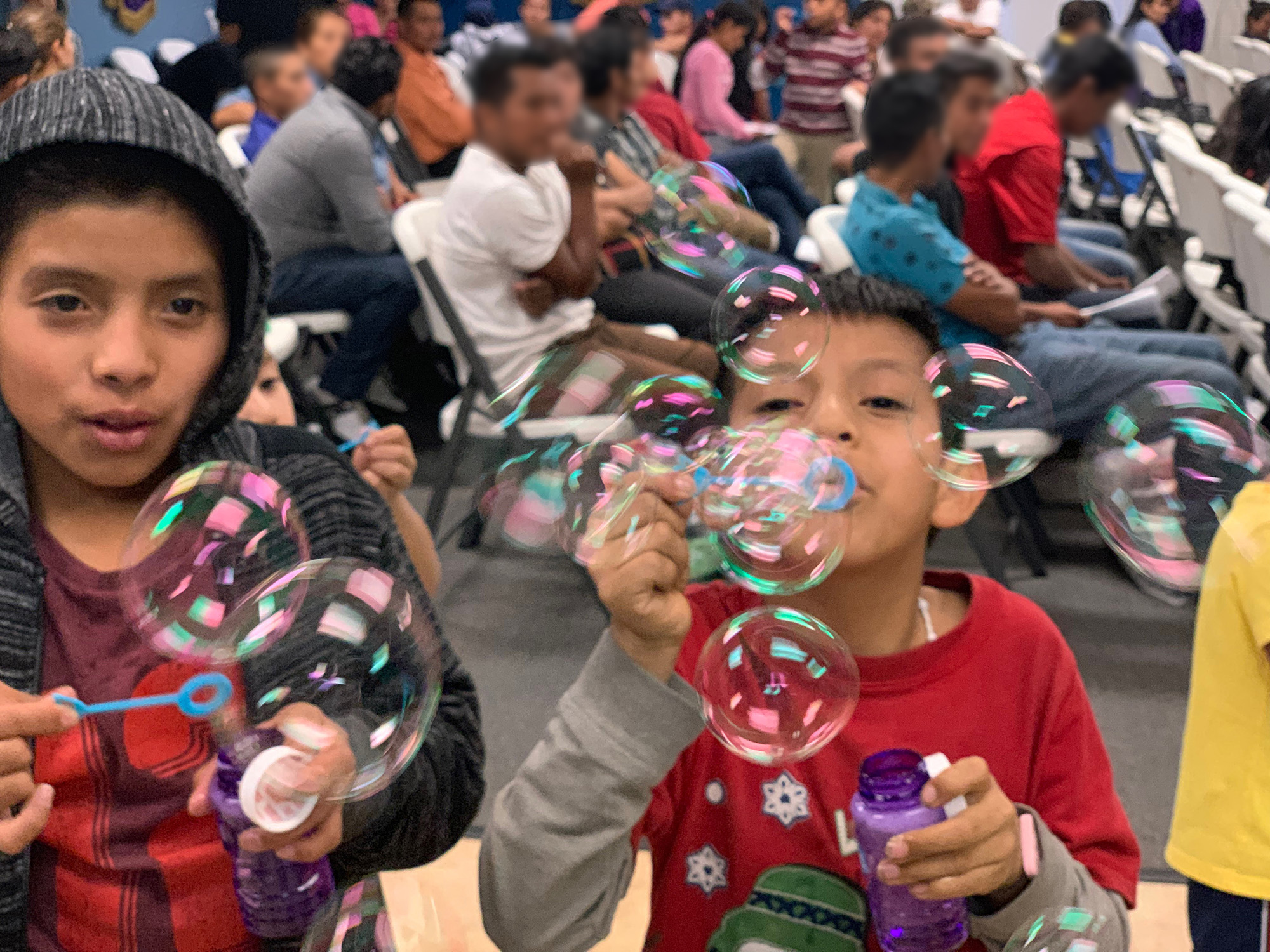 Without complaint, asylum seekers sat quietly in rows of chairs in the church sanctuary waiting for instructions and assistance, and patiently enduring—sometimes enjoying—the bubble-blowing exuberance of the children.