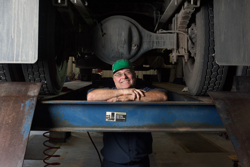 A mechanic poses between the tires. This image I am using a 45 degree angle of lighting and using natural light in the machine shop for fill.