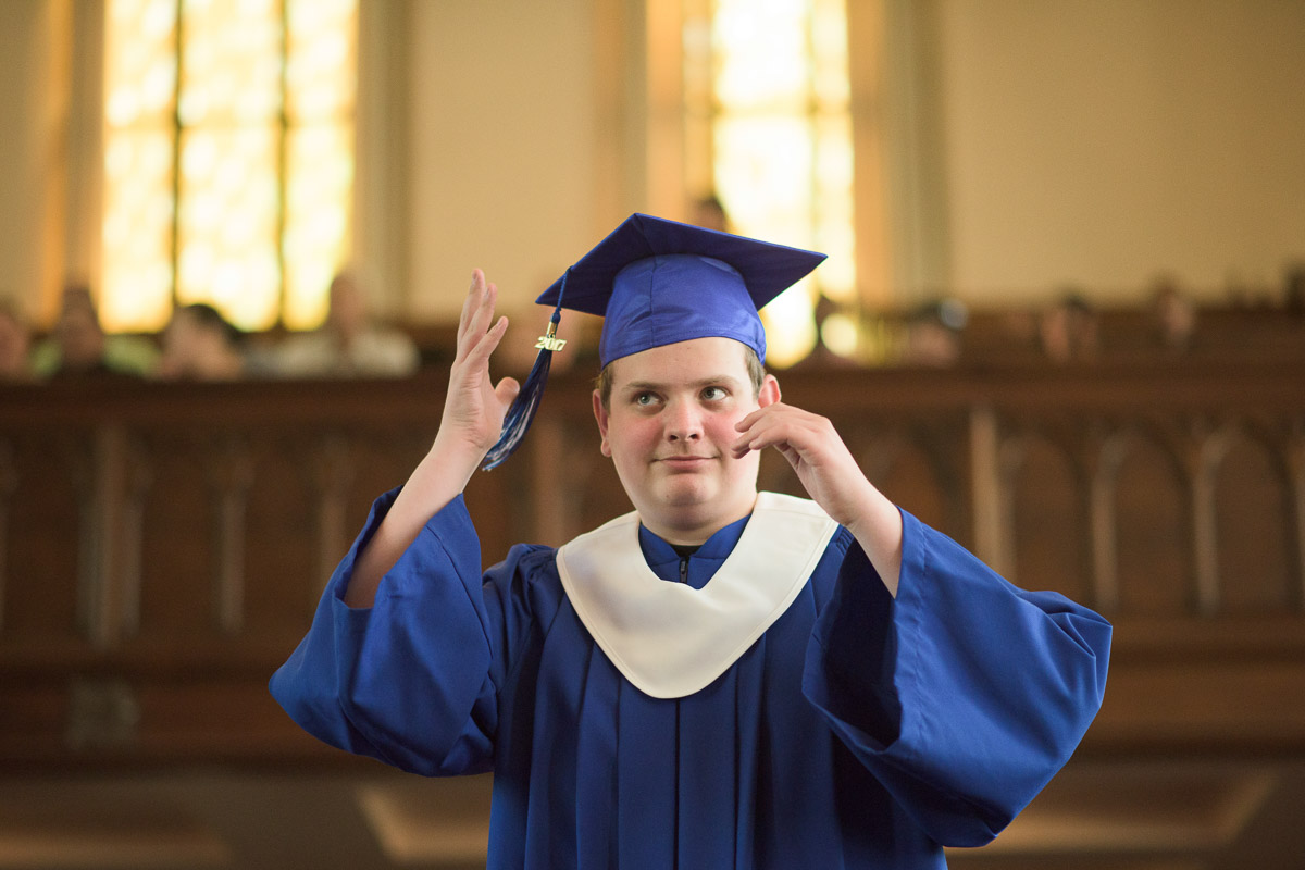 In this candid shot, a graduate moves the tassel on their graduation cap from one side to the other, signifying that they have received their diploma.