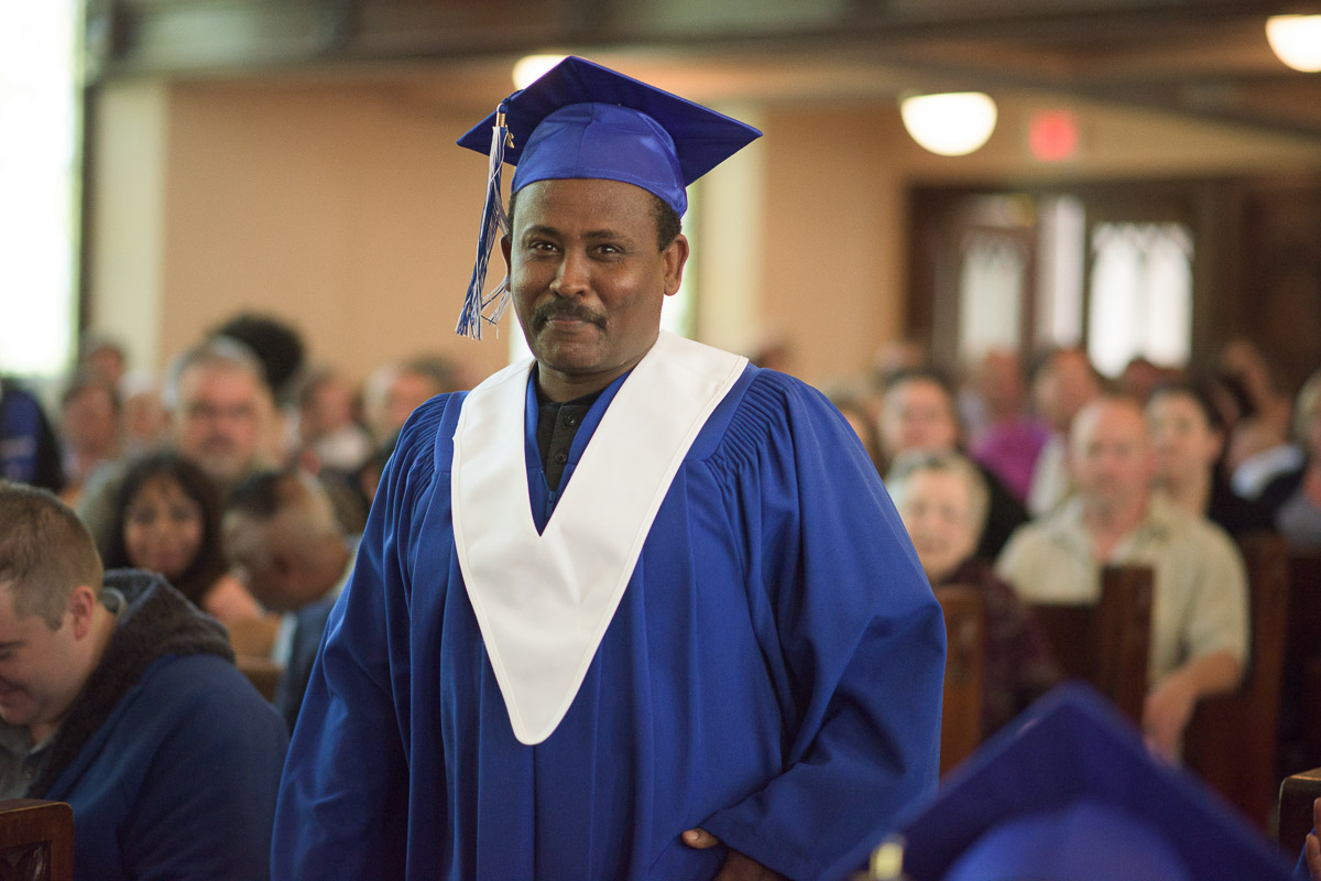 A student stands, preparing to approach the stage. The warm smile on the graduand's face evokes a sense of pride and anticipationt. A shallow depth of field is used to bring the student into focus and softly blur the seated guests in the background.