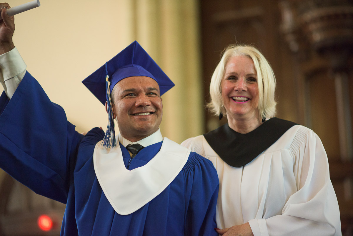 In this action shot, a new graduate raises their diploma, victoriously, with an instructor at their side.