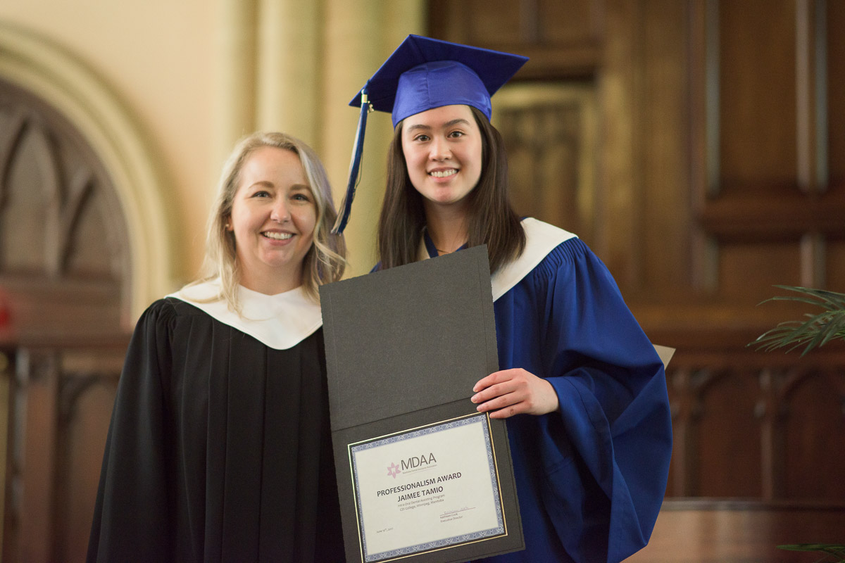 An instructor poses with a student holding an award certificate.
