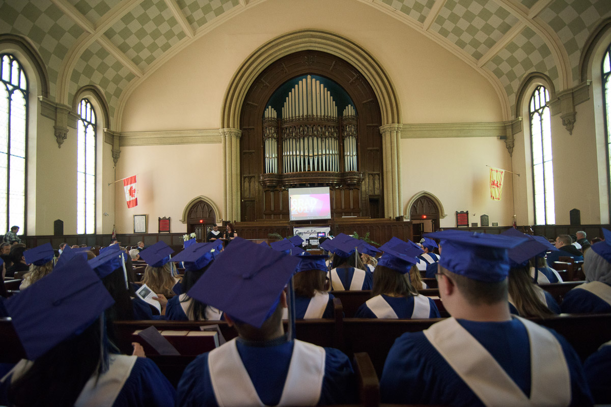This photograph captures the rows of seated students and the area above them reaching up to the high vaulted ceiling. This perspective emphasizes the architectural features of the space, and provides a sense of its size and the number of people in the room.