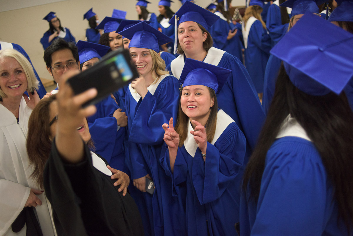 There is a lot of activity in this photograph, which features a group of students and instructors taking a group shot using a phone. The photograph conveys the celebratory atmosphere of the event.