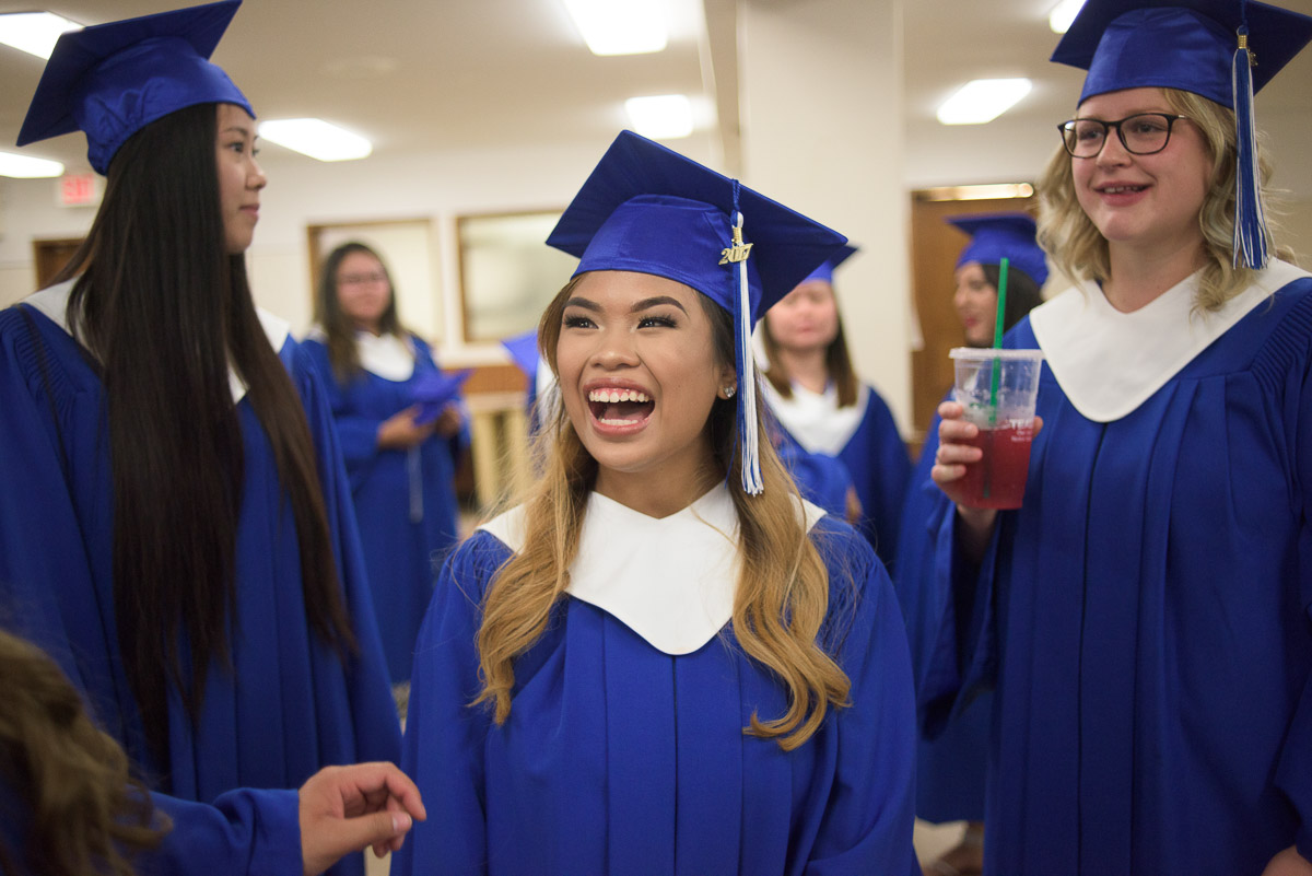 This candid image captures a group of graduates sharing in a laugh following the ceremony. The smiling faces help to convey the exuberance of the day.
