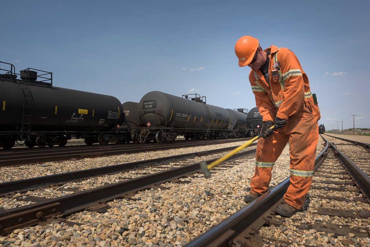 An employee in an orange jumpsuit and hard hat works on the tracks. The rails create leading lines in the photograph, guiding the eye to the employee hard at work. Tank cars line the tracks behind him.