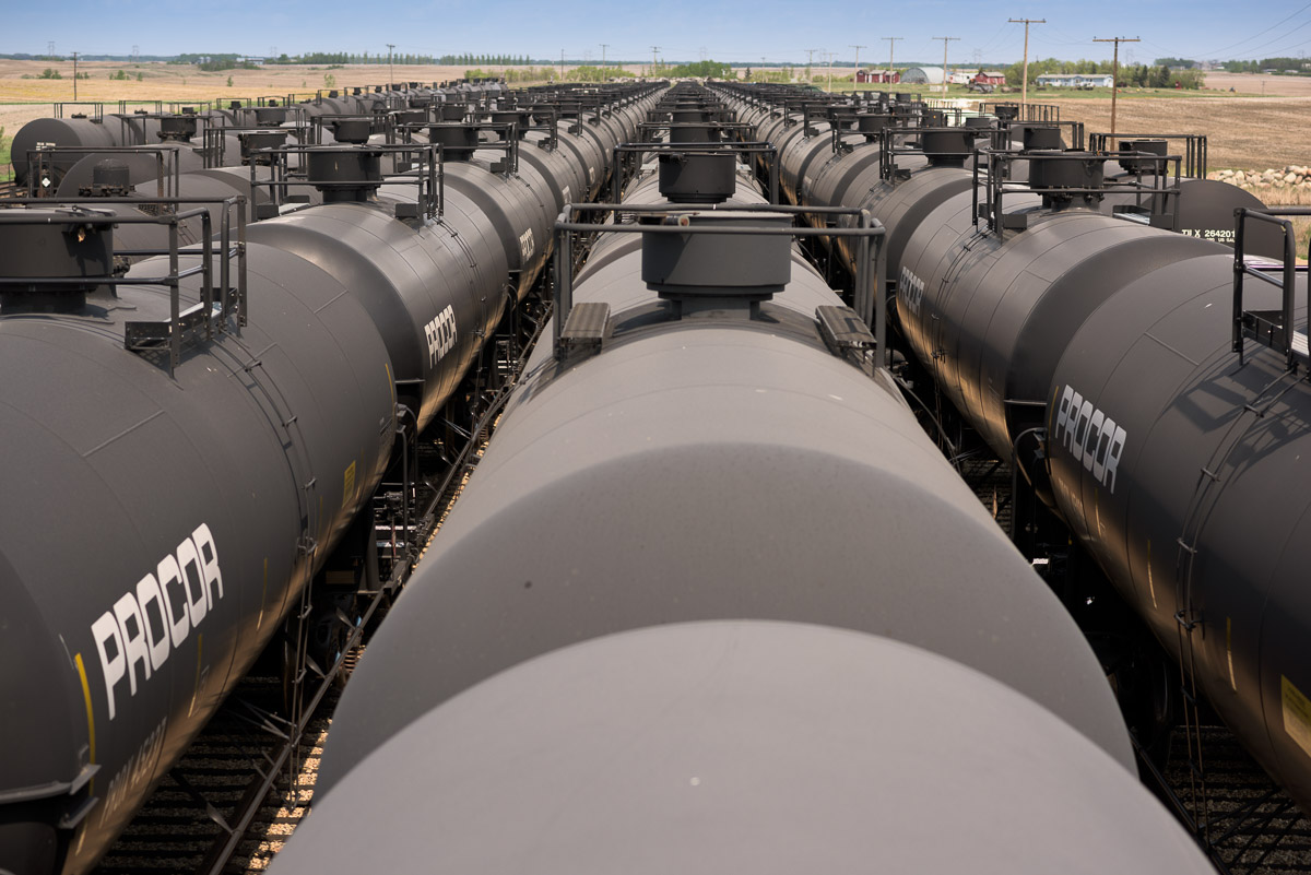 This image captures the view from on top of a tank car. The leading lines of the grey, cylinder-shaped, tank cars guide the eye towards the horizon. It is a powerful image, with the rows of train cars lining the tracks as far as the eye can see.