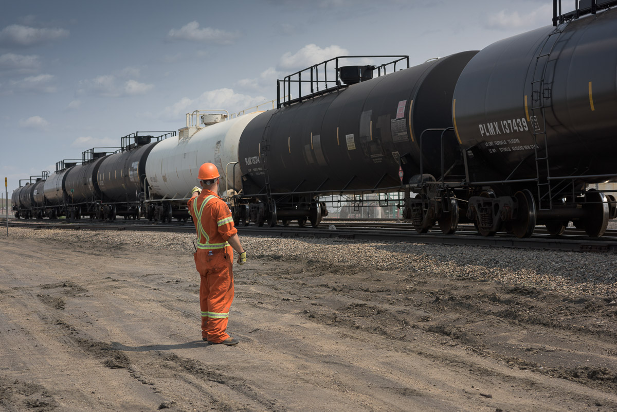 In this full shot image, an employee monitors activity in the yard, as a train moves along the track.