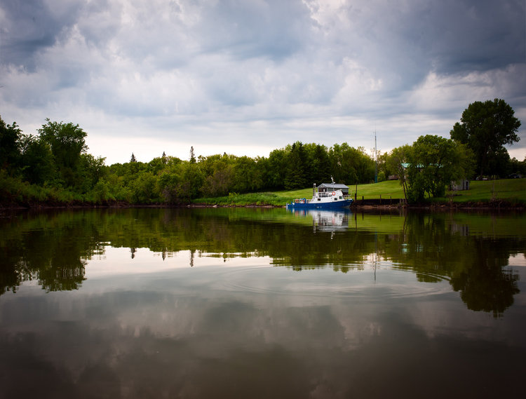 Boat In Selkirk Manitoba  A fishing boat sits docked during a storm in Selkirk Manitoba. The reflection of the water reflects the scene.