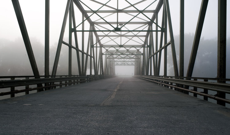 Fog rolls in the early morning on a bridge somewhere near St. Eustache, Manitoba.