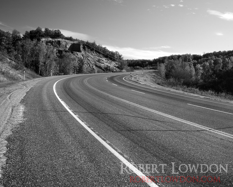 The road winds through the hills of the Pembina valley in southern Manitoba.