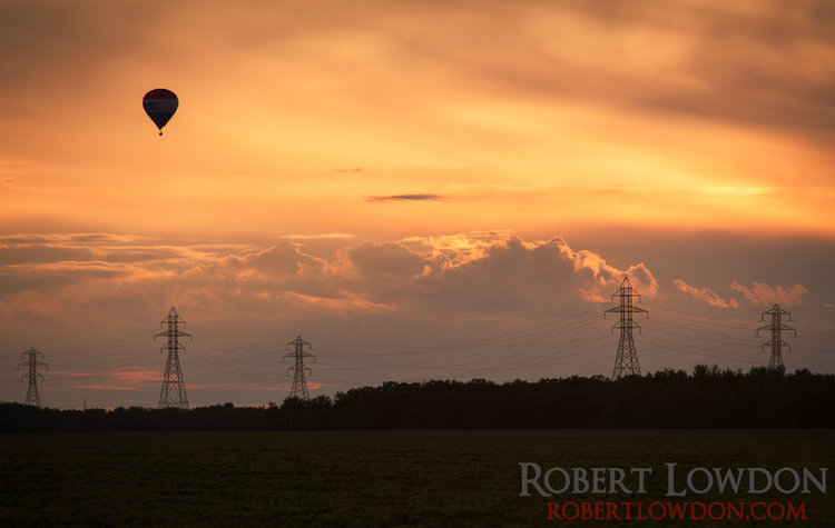 The Great Winnipeg Balloon Attack.  The sun sets over the prairies with a hot air ballon in the background