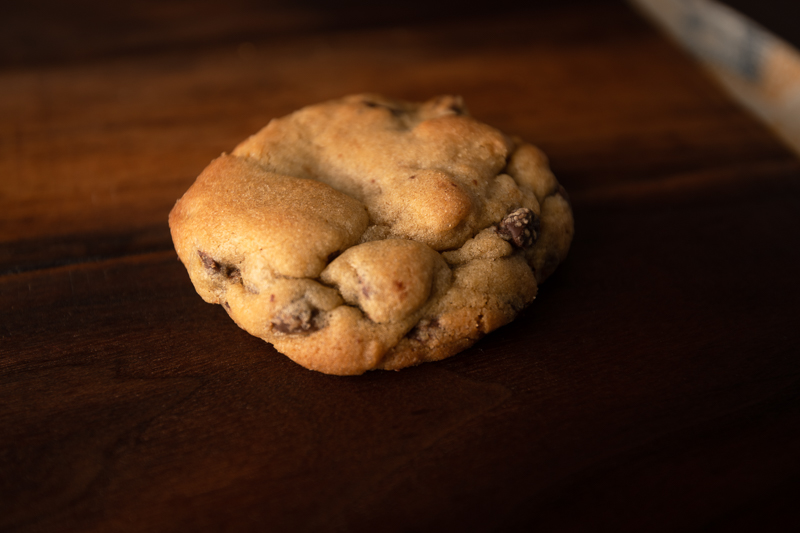 A single chocolate chip cookie sits on a wood board. © Robert Lowdon