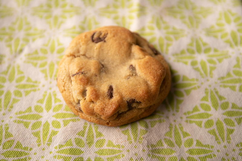 A single chocolate chip cookie on a table cloth. © Robert Lowdon