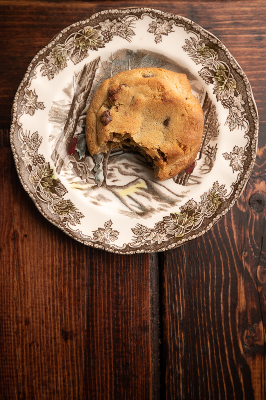 A cookies with a bite missing on a plate. © Robert Lowdon
