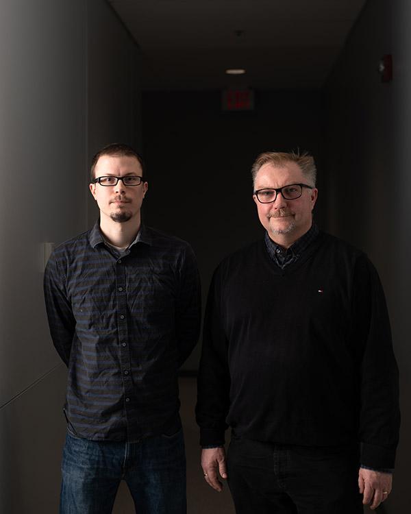 Two team members in a dark hallway